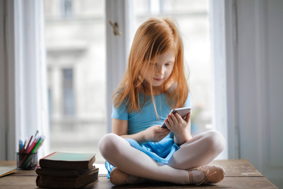 pige som sidder med en telefon